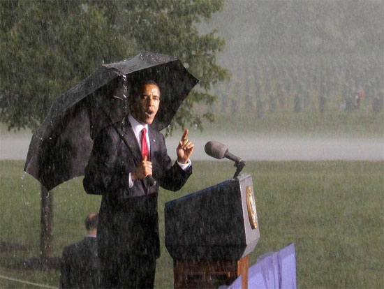 Obama, with cemetery in background, shows what a real President looks like, standing in the rain